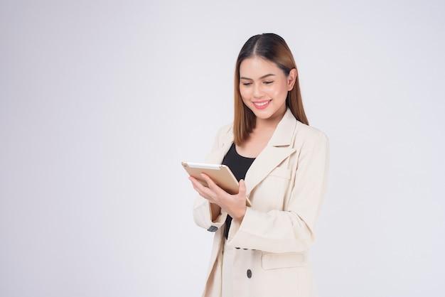 Giovane bella donna di affari in vestito che tiene compressa sopra il fondo bianco dello studio?