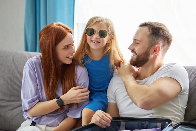 Giovane e bella famiglia caucasica con la valigia dell'imballaggio del bambino