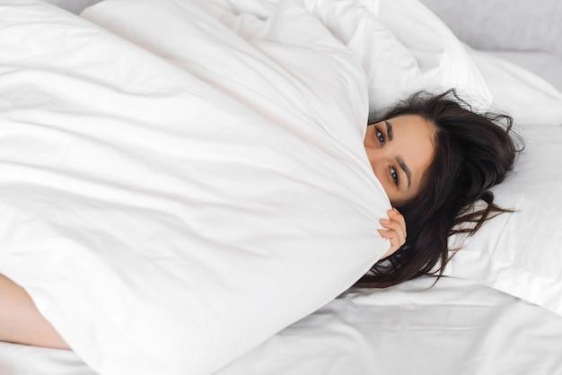 La giovane bella ragazza caucasica guarda fuori da sotto la coperta su un letto bianco