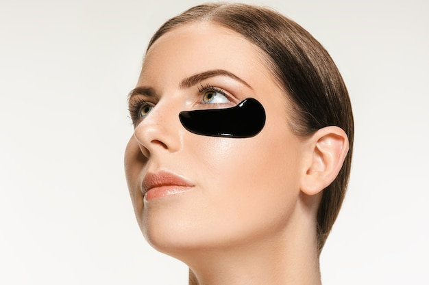 Giovane bella donna caucasica che applica una maschera cosmetica nera per il viso del fango nero terapeutico. trattamento termale e concetto di bellezza del viso. cura del viso femminile e concetti di pelle perfetta