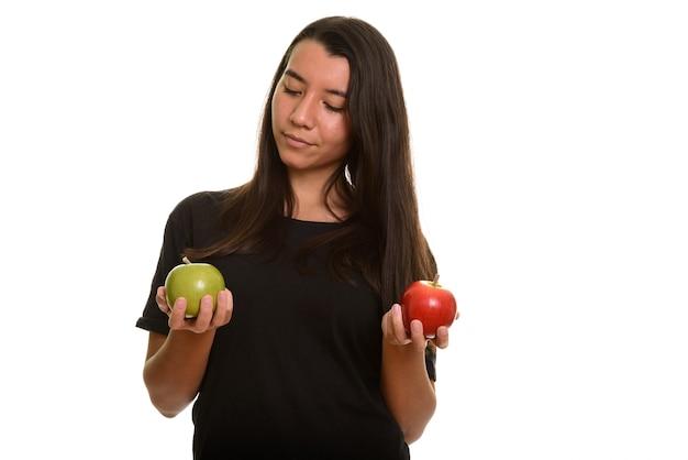 Giovane bella donna caucasica scegliendo tra mela rossa e verde