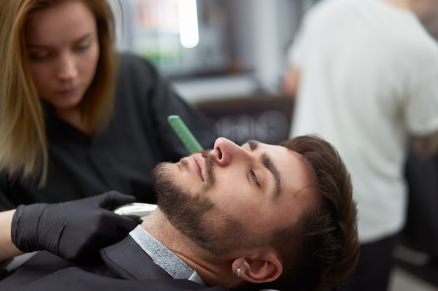 Il parrucchiere della giovane bella donna caucasica taglia l'uomo bello della barba al moderno negozio di barbiere