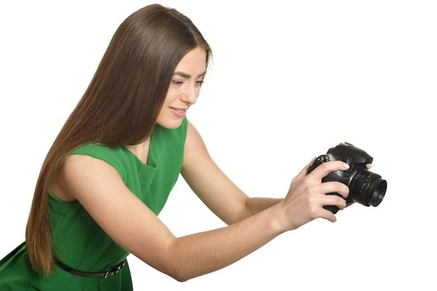 Giovane bella donna caucasica con fotocamera su sfondo bianco