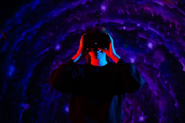Giovane bella ragazza felice allegra in occhiali per realtà virtuale con luci blu e rosse nella stanza dei giochi
