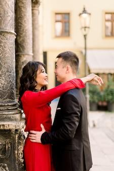 Giovani belle coppie cinesi nell'amore che si abbraccia sulla vecchia via della città