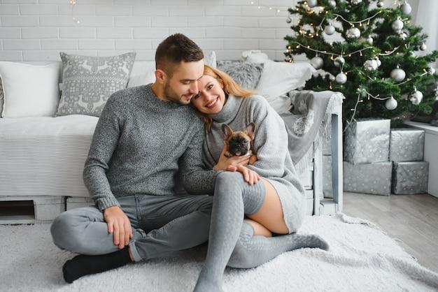 Giovane bella coppia sta giocando con il loro cane nel soggiorno festivo di capodanno appena prima di natale