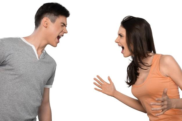 Giovane bella coppia che litiga e urla con l'espressione facciale, isolata su sfondo bianco