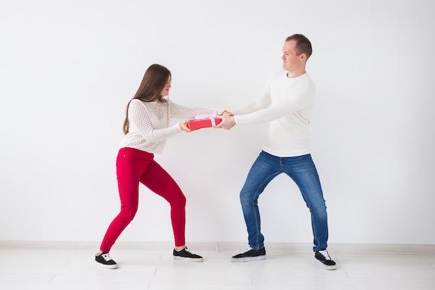 Giovane bella coppia in lotta per il regalo di natale su sfondo di legno.