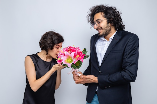 Giovane bella coppia uomo felice che dà un mazzo di fiori alla sua adorabile fidanzata che celebra la giornata internazionale della donna l'8 marzo in piedi su sfondo bianco
