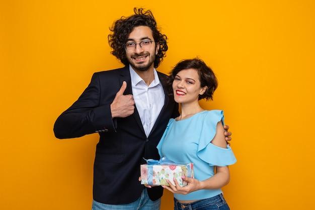 Giovane bella coppia uomo felice che mostra i pollici in su sorridente higging la sua ragazza sorridente con presente nelle mani per celebrare la giornata internazionale della donna 8 marzo in piedi su sfondo arancione