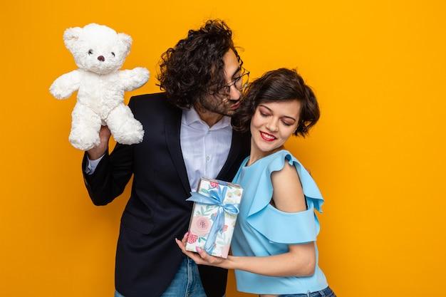 Giovane bella coppia uomo felice con orsacchiotto che bacia la sua ragazza sorridente con presente che celebra la giornata internazionale della donna 8 marzo in piedi su sfondo arancione