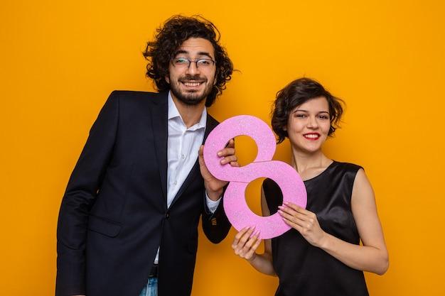 Giovane bella coppia felice uomo e donna che tiene il numero otto guardando la telecamera sorridendo allegramente per celebrare la giornata internazionale della donna 8 marzo in piedi su sfondo arancione