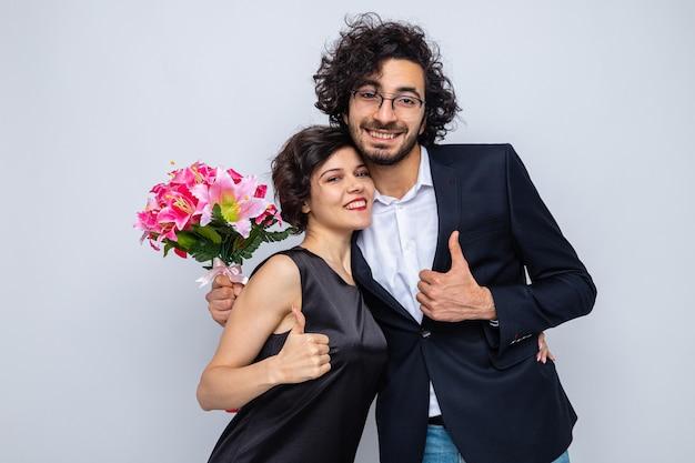 Giovane bella coppia felice uomo e donna con bouquet di fiori che guarda l'obbiettivo sorridente allegramente mostrando pollice in alto celebrando la giornata internazionale della donna 8 marzo in piedi su sfondo bianco