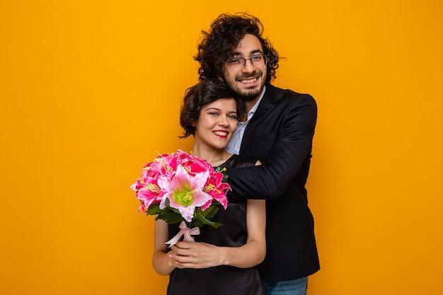 Giovane bella coppia felice uomo e donna con bouquet di fiori sorridente allegramente abbracciando felice in amore celebrando la giornata internazionale della donna 8 marzo in piedi su sfondo arancione
