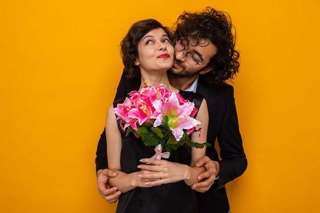 Giovane bella coppia felice uomo e donna con bouquet di fiori sorridenti allegramente abbracciati felici innamorati