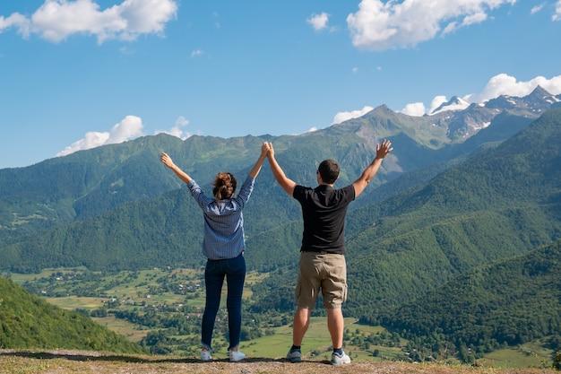 Giovani, belle coppie che tengono le mani in aumento in alte montagne della parte superiore di svaneti, georgia. viaggio.