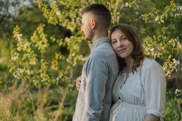 Giovani belle coppie che abbracciano nel giardino di primavera