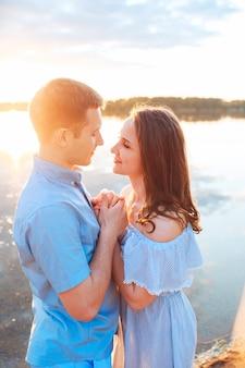 Giovani belle coppie nell'amore che bacia sulla spiaggia