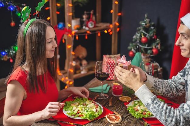 Giovane bella coppia di innamorati sta trascorrendo una festosa cena di natale