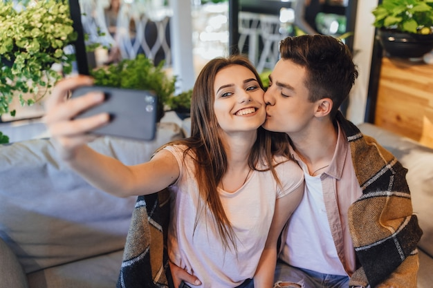 Una giovane bella coppia fa selfie sulla terrazza estiva di un moderno caffè