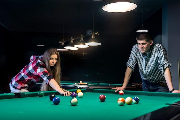 Giovane e bella coppia giocando a biliardo al bar