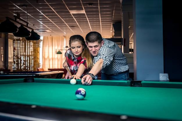 Giovane e bella coppia che gioca a biliardo insieme