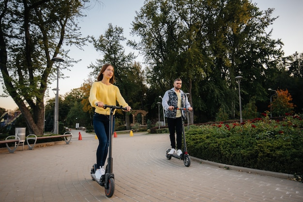 Una giovane bella coppia cavalca scooter elettrici nel parco in una calda giornata autunnale