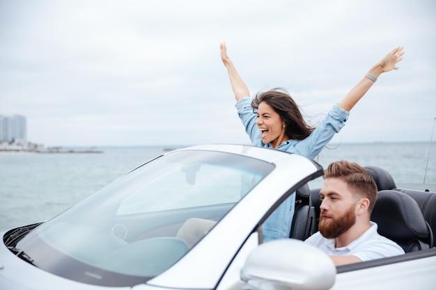 Giovane bella coppia in viaggio su strada guidare in macchina insieme