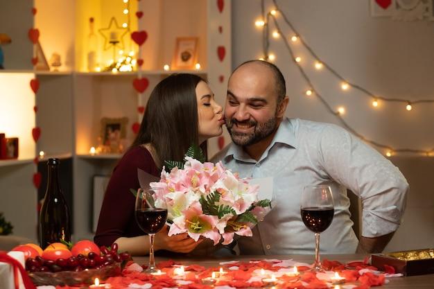Giovane bella coppia seduta al tavolo decorato con candele e petali di rosa uomo felice dando un mazzo di fiori