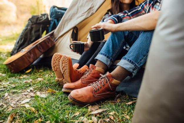 Giovane bella coppia seduta in tenda in campeggio