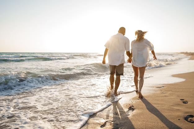 Giovane bella coppia che cammina sulla spiaggia vicino al mare