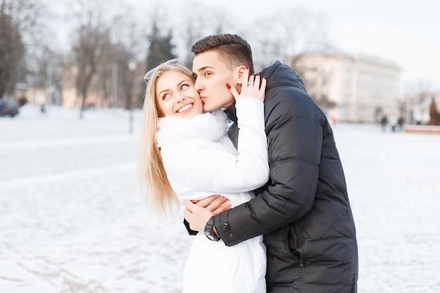 Giovane bella coppia nella fredda giornata invernale a piedi in città