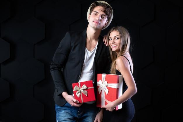 Giovane bella coppia con doni in mano su uno sfondo nero. vacanza. Foto Premium
