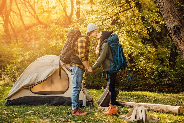 Giovane bella coppia con zaino da trekking che si bacia nella foresta vicino alla tenda