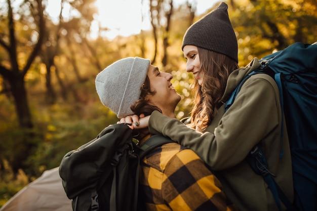 Giovane bella coppia con zaino da trekking che si bacia nella foresta