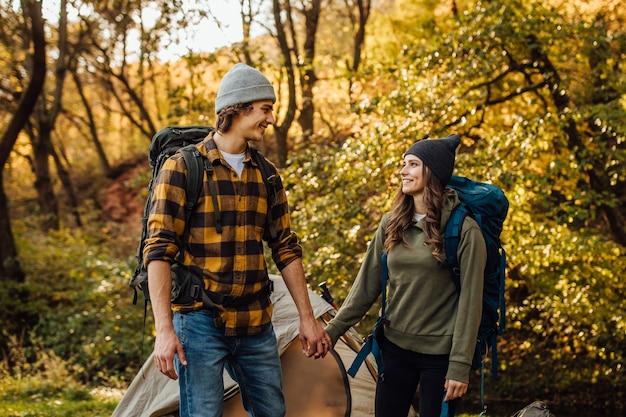 La giovane bella coppia con gli zaini da trekking va a fare escursioni