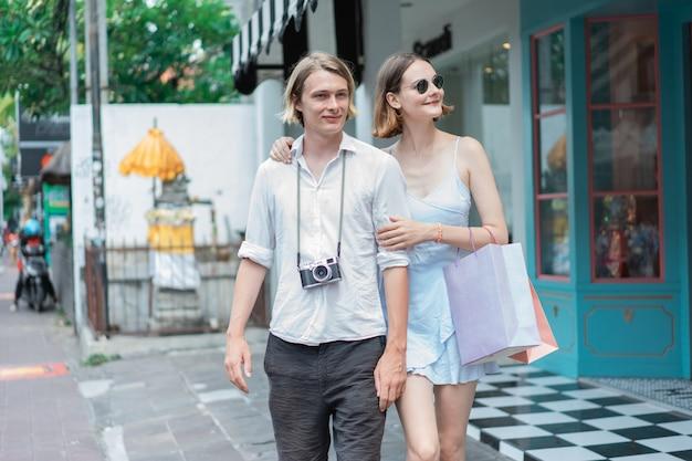 Giovani belle coppie con i sacchetti della spesa nella città