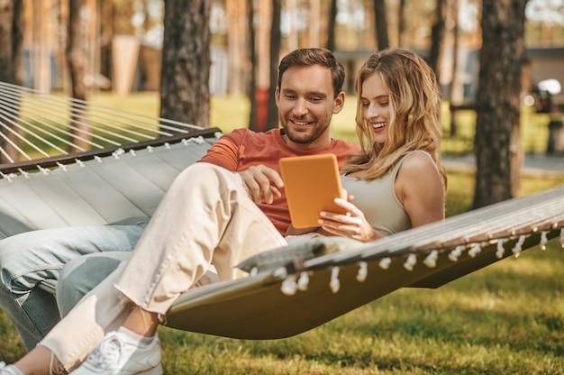 Giovane bella coppia con tablet sull'amaca