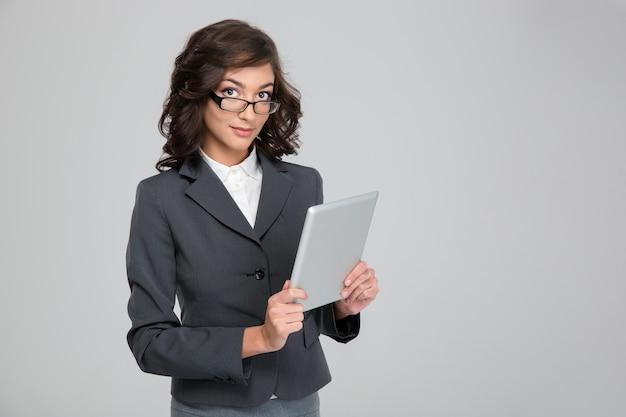 Giovane bella donna d'affari riccia in giacca grigia e occhiali usando tablet
