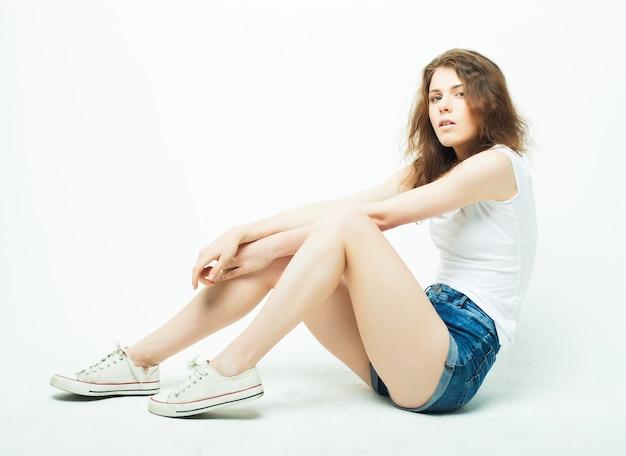 Giovane bella donna riccia in posa con t-shirt bianche, ower muro bianco