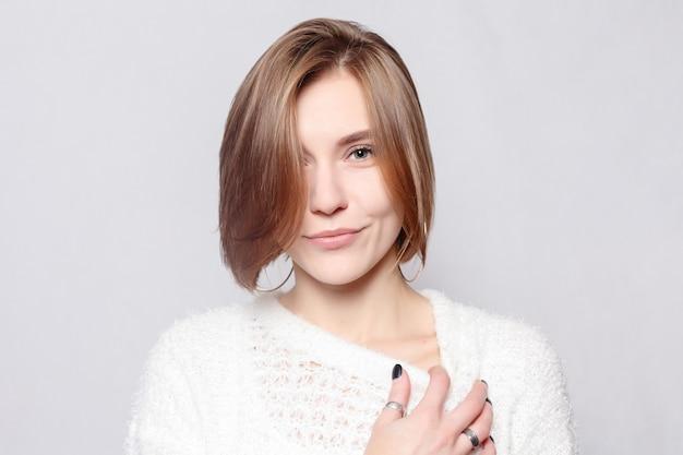 Giovane bella ragazza carina che mostra emozioni diverse. sfondo per ragazza un muro grigio cemento.