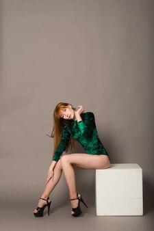 Giovane bella ballerina in posa in uno studio su sfondo grigio