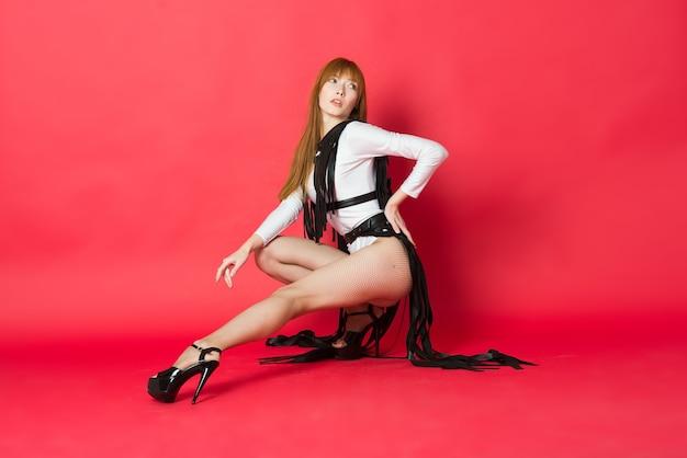 Giovane bella ballerina in posa in uno studio sul rosso