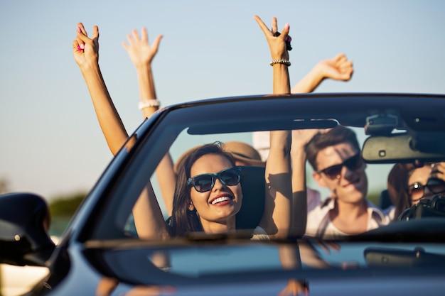 Giovani belle giovani donne dai capelli scuri con amici in occhiali da sole sorridono e cavalcano in una cabriolet nera sulla strada tenendosi per mano in una giornata di sole. .