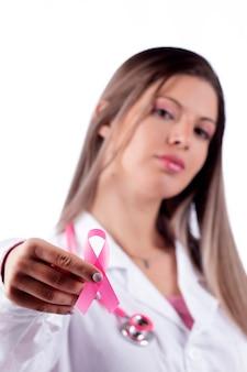 Giovane bella donna medico con stetoscopio rosa e nastro rosa di consapevolezza per il cancro al seno.