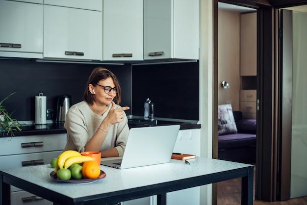 La giovane bella donna europea in vetri alla moda lavora con il computer portatile nella cucina domestica. comunicare con amici e parenti online tramite internet. interni minimalisti nei toni del beige.