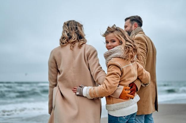 Giovane bella famiglia guarda il mare che abbraccia, vestita di sciarpe e cappotti in inverno.