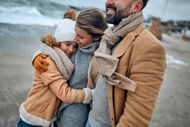 La giovane bella famiglia guarda il mare abbracciata, vestita con sciarpe e cappotti in inverno.