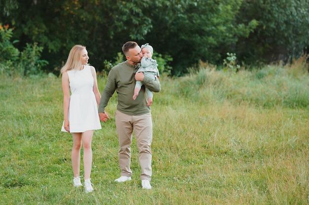 Giovane bella famiglia con una piccola figlia che abbraccia, bacia e cammina nella natura al tramonto. foto di una famiglia con un bambino piccolo in natura.