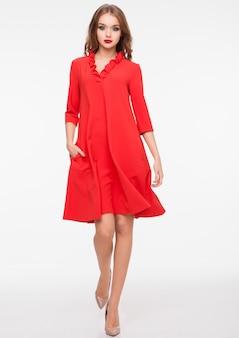 Giovane bello modello di moda che porta vestito rosso su bianco